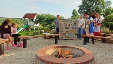 Na zdjęciu miejsce na ognisko wykonane z kamienia i cegły, w tle kaszubi śpiewający kaszubskie nuty